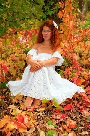 Beautiful red-haired young woman, wearing in white dress or the bride and decoration in form of flower on her head sitting among red leaves in autumn forest. photo
