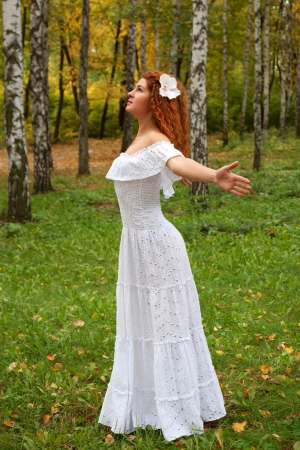 Beautiful red-haired young woman, wearing in white dress or the bride and decoration in form of flower on her head looking up, arms. as if flying. The concept of happiness and freedom. photo