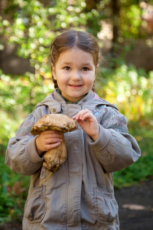 Little girl holding big edible mushroom  boletus in autumn forest. Stock Photo - 15922262