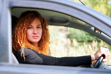 Beautiful red-haired young red-haired woman driving car Stock Photo - 15937405