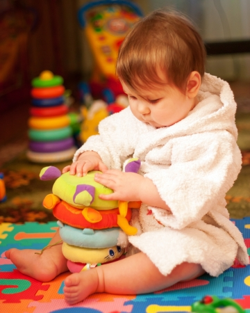 Lovely chubby baby in bathrobe after bath playing with toys on the floor .. Stock Photo - 16250111
