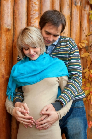 Young pregnant couple in love against the backdrop of a log fence. Selective focus on the happy faces of the people. photo