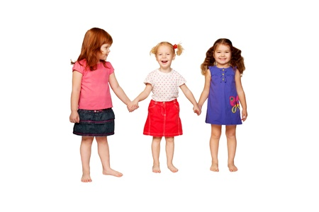 Three lovely smiling little girls holding hands, redhead, blonde and brunette  Isolated on white background photo