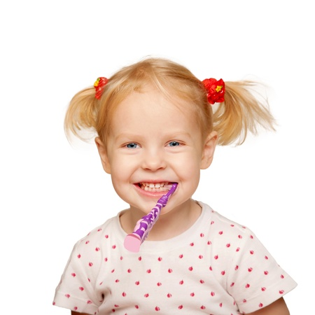 Pretty little girl brushing teeth  Isolated on white background photo