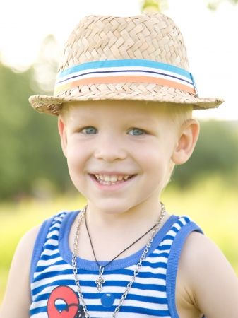 Portrait of young cute boy with blue eyes, wearing a straw hat. Stock Photo - 16524143