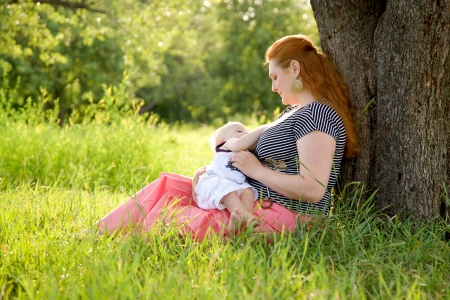 Happy mother and baby with Down syndrome hugging and kissing under the tree on the grass in the park. photo