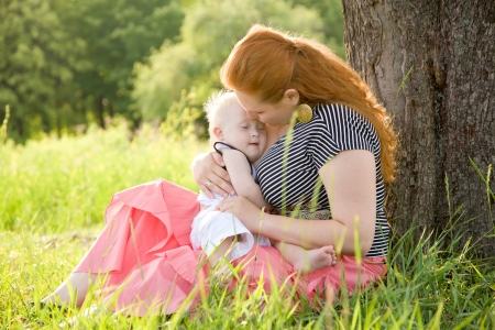 Happy mother and baby with Down syndrome are lying on the grass in the park. photo
