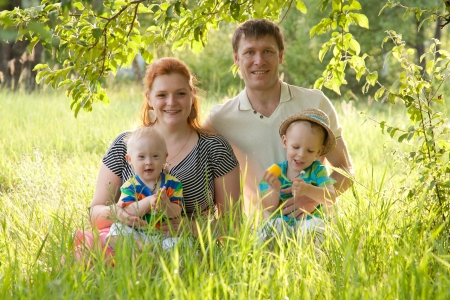 syndrome: Big happy family - mother, father and children sitting in the grass under a tree in the park. One of the kids - with Down syndrome. Stock Photo