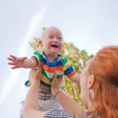 naar beneden kijken: baby met het syndroom van Down is gelukkig en vliegt omhoog