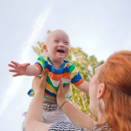 handicapped person: baby with Down syndrome is happy and flying up
