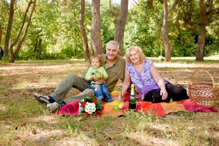 Happy elderly couple picnicking in the forest photo
