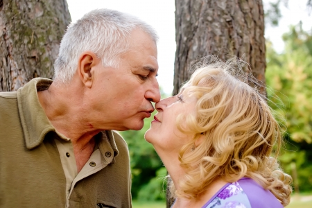 Happy lovely elderly senior couple kissing in park Stock Photo