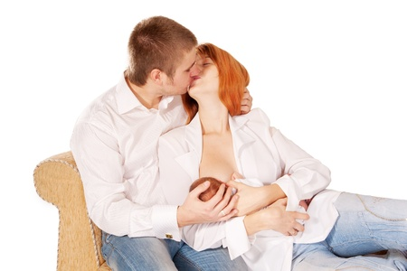 lactation: Happy family, father, mother and newborn baby  Parents kissing, baby eating Isolated on white background  Family concept  Stock Photo