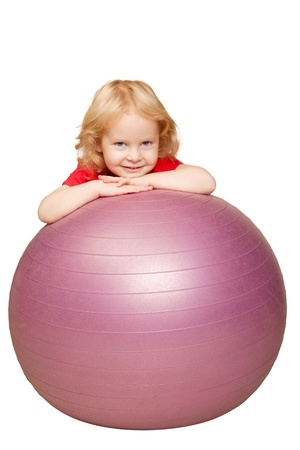 Adorable curly blond baby with blue eyes smiling and playing with fitness ball  Isolated on white background photo