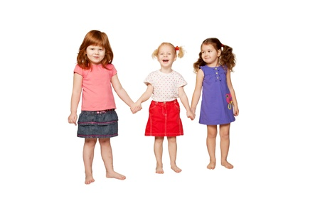 girls holding hands: Three girlfriends, lovely smiling little girls holding hands, redhead, blonde and brunette  Isolated on white background  Stock Photo