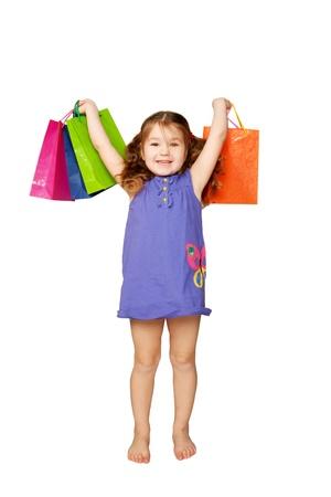 ni�os de compras: Ni�o feliz con bolsas de la compra Ella est� disfrutando de los regalos y las vacaciones aisladas sobre fondo blanco