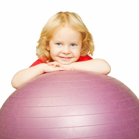 Healthy lifestyle. Child playing sports, smiling and resting on fitball. Isolated on white background photo