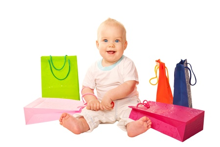 Baby shopping  Happy smiling kid sitting with shopping bags  Isolated on white background