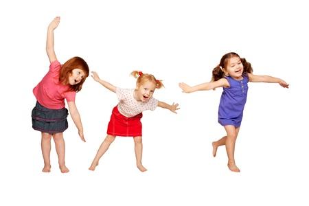 chicas bailando: Felices los ni�os peque�os bailando pelirroja, partido muchachas alegre rubia y morena aislado sobre fondo blanco