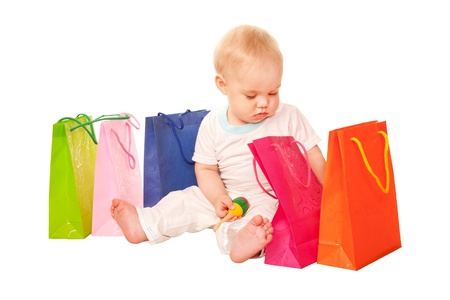 Baby shopping  Happy child sitting with shopping bags, examining purchase  Isolated on white background photo