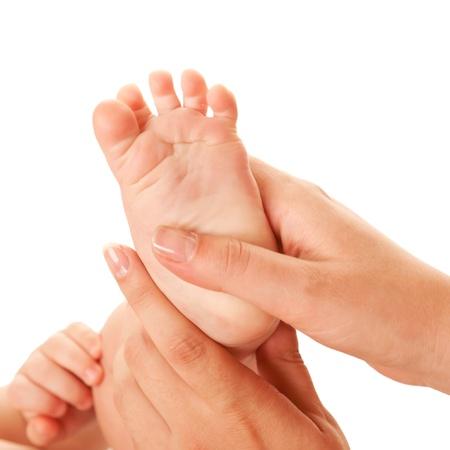 pie bebe: Madre haciendo masaje en los pies del beb� aislado en el fondo blanco