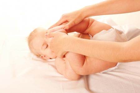 massage enfant: Bébé Mère gymnastique faire de l'exercice, toucher les pieds du bébé s à la tête Isolé sur fond blanc Banque d'images
