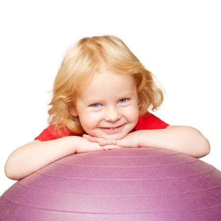 CHILD CARE: Happy child with fitness ball playing sports   Isolated on white background