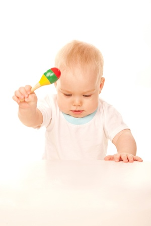 Baby knocking his rattle on the table. Isolated on white background. Stock Photo - 17059979