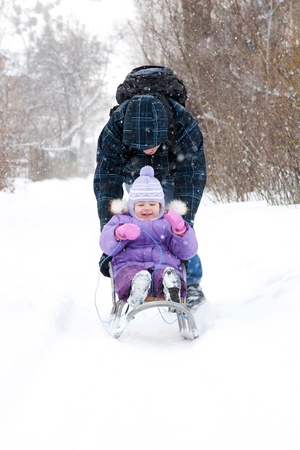 Father rolling a small child on a sled in the winter. Its snowing. photo