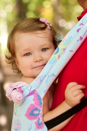 Happy baby sitting in a carrying sling. Father carry a child comfortable. Walking outdoors. Selective focus on the face of the baby. Stock Photo