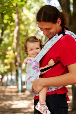 baby carrier: Happy baby sitting in a carrying sling. Funny father and baby walking outdoors. Father carry a child comfortable. Selective focus on the face of the baby.