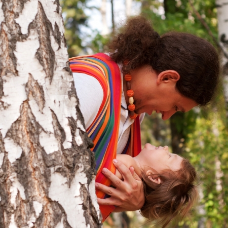 baby carrier: Happy father and kid playing and laughing in forest. Baby sitting in a sling. Stock Photo
