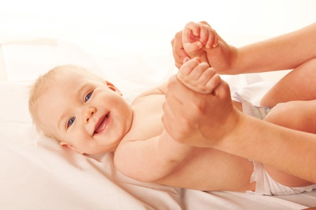 baby massage: Gymnastique pour le b�b�. M�re faire de l'exercice, gamin souriant. Isol� sur fond blanc.
