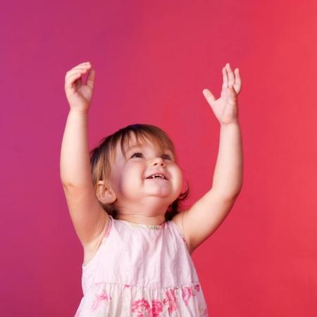 Baby vangen iets met zijn handen omhoog. Blij gezicht close-up.