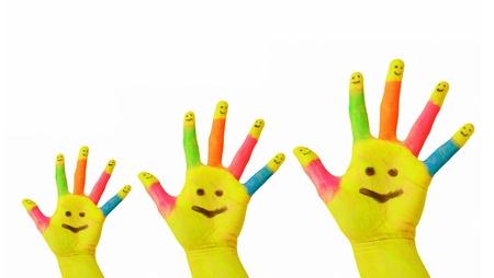 manos sucias: Familia feliz, sonrisas felices. Padre, madre, bebé coloridos manos pintadas con cara sonriente dibujada en las palmas y dedos amarillos cada uno. La alegría y la diversión. Aislado sobre fondo blanco