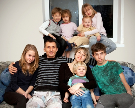 large woman: Happy big family. Father, mother and seven children at home. Family concept.