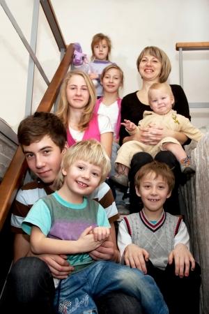 Grote, gelukkige familie - een moeder en veel kinderen zitten op de trap thuis. Family concept.