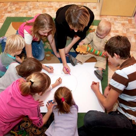 Grote, gelukkige familie - een moeder en zeven kinderen het tekenen van een hart samen thuis. Family concept.