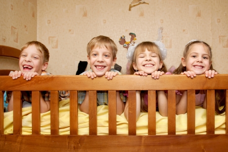 triplet: Four children, two brothers and two sisters lying on the bed, looking over a side and laughing. Happy family. Triplet and their older sister.