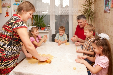 a big family: Happy big family cooking a pie together. Father, mother and four children, two boys and two girls playing with dough in the kitchen. Stock Photo