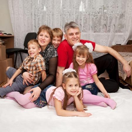 Glimlachend gelukkig grote familie thuis. Vader, moeder en vier kinderen, twee jongens en twee meisjes.