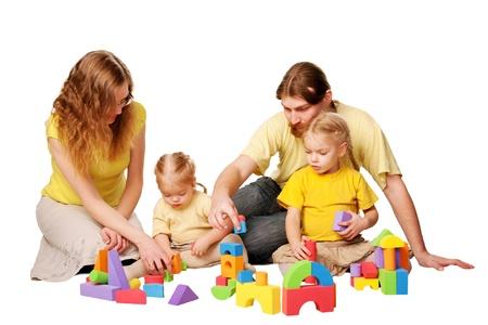 Gelukkige vader, moeder en twee kinderen bouwen van speelgoed blokken Family concept geïsoleerd op witte achtergrond