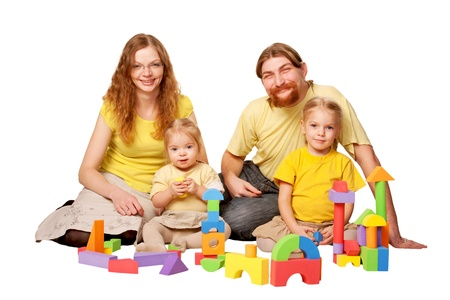 Happy father, mother and two children building from toy blocks  Family concept  Isolated on white background photo