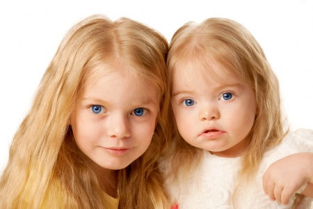 down syndrome: Two lovely sisters  Preschooler and baby girl   Isolated on white background
