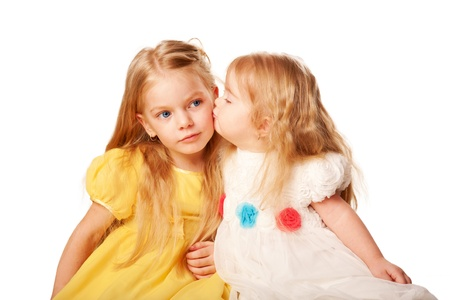 Two lovely sisters in elegant dresses  Preschooler and baby girl  Younger sister kissing elder sister   Isolated on white background photo