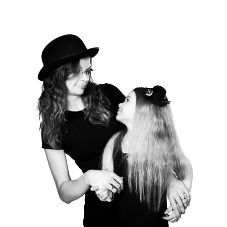 alike: Stylish mother and daughter, wearing a hat, looking face to face each other  Black and white portrait  Retro style  Isolated on white background Stock Photo