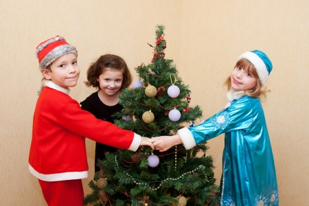 Children in carnival costumes dancing around the Christmas tree. photo