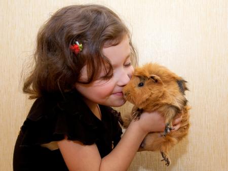Het meisje kussen van de cavia. Liefde voor dieren concept.