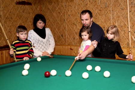 twin sister: Happy family playing in the billiards. Father, mother and three children, triplets. Father teaching kids  the game. Stock Photo