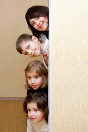 hands behind head: Mother and three children peeking of the door.